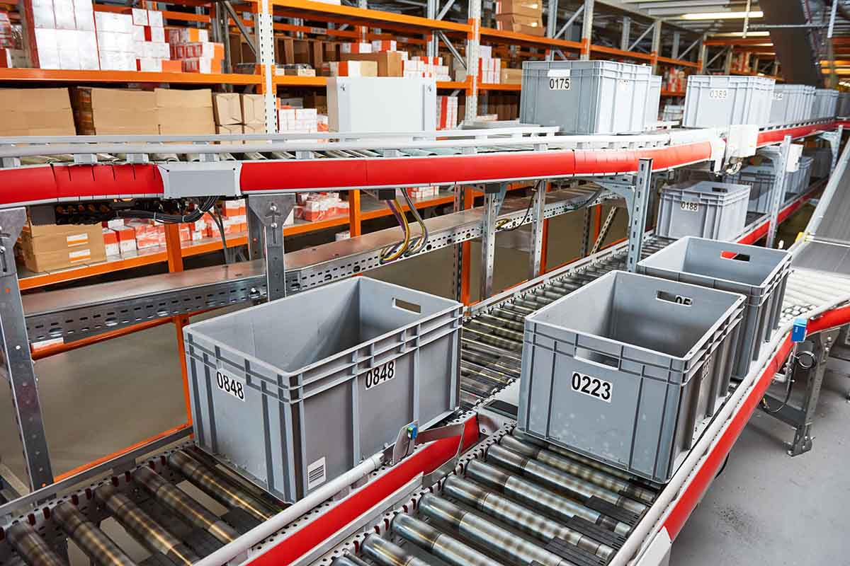 Automated warehouse. Boxes with spare parts moving on conveyer.