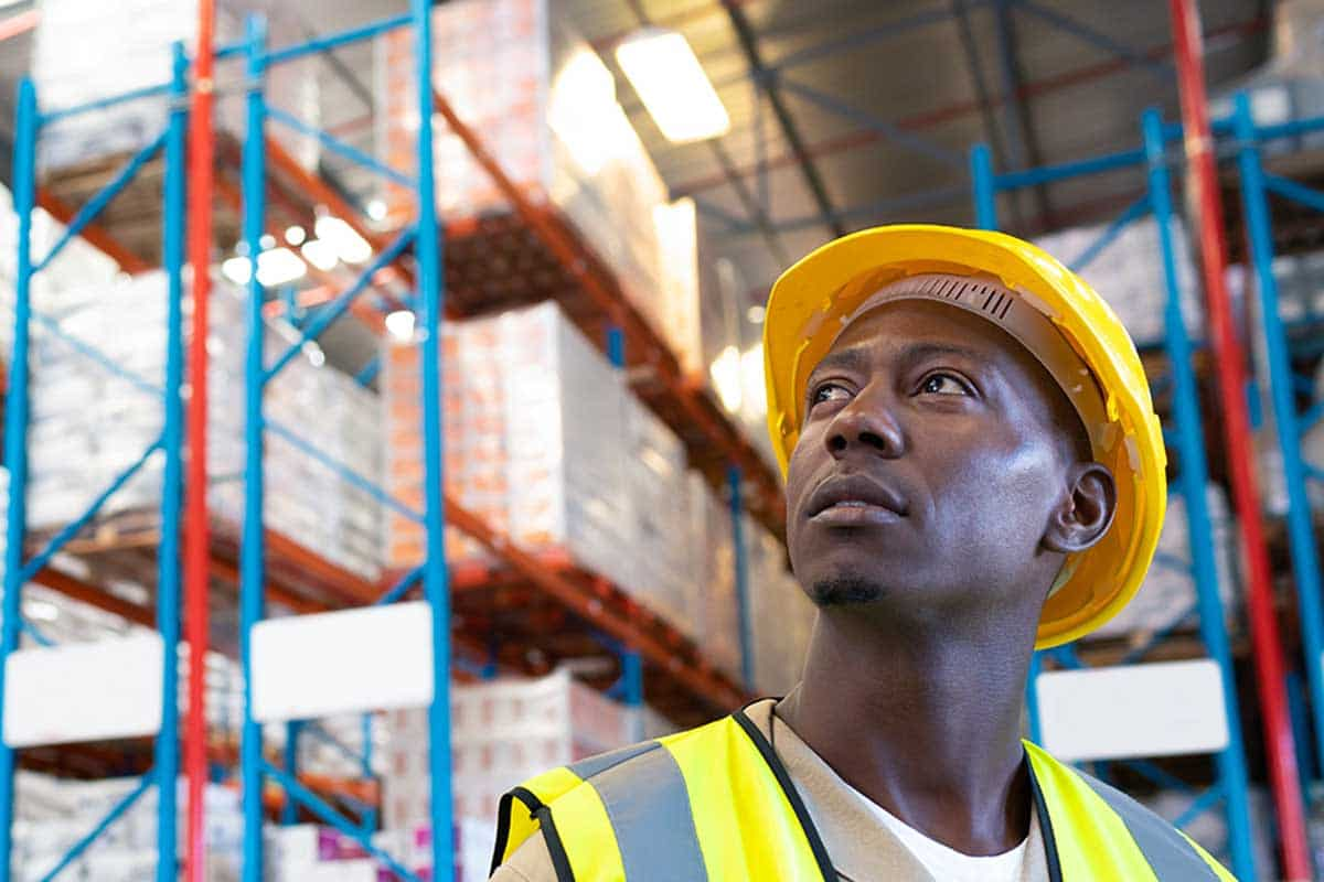 Thoughtful male worker looking away in warehouse