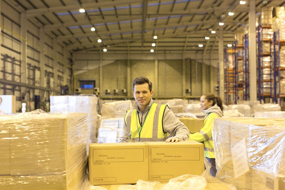 Worker unpacking boxes in warehouse