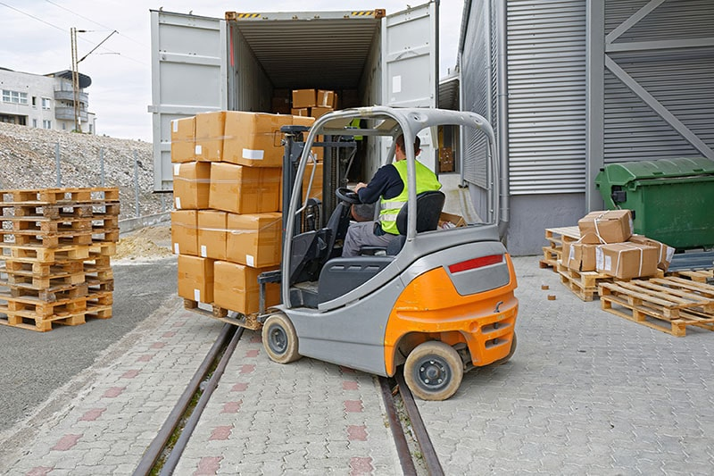 forklift and driver unloading packages