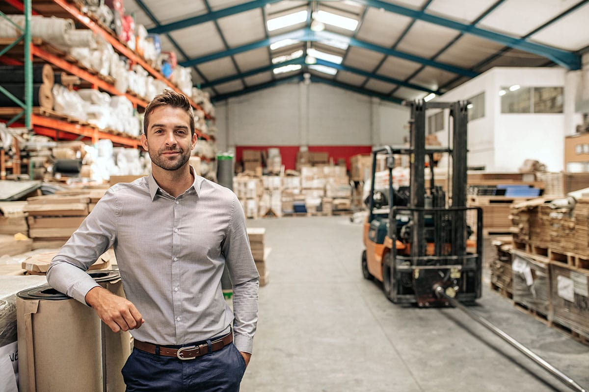 Smiling manager leaning against stock in a large warehouse